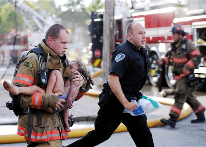 A firefighter rushes an injured boy to a waiting ambulance after being injured in a house fire. Image courtesy of www.firstresponderwellness.com.