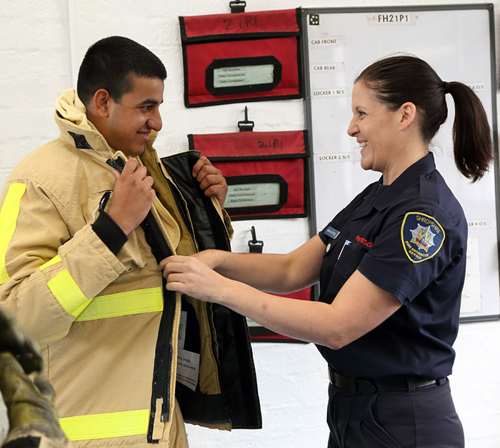 Akib Ali tries on a firefighter's jacket for size from firefighter Sarah Cattell