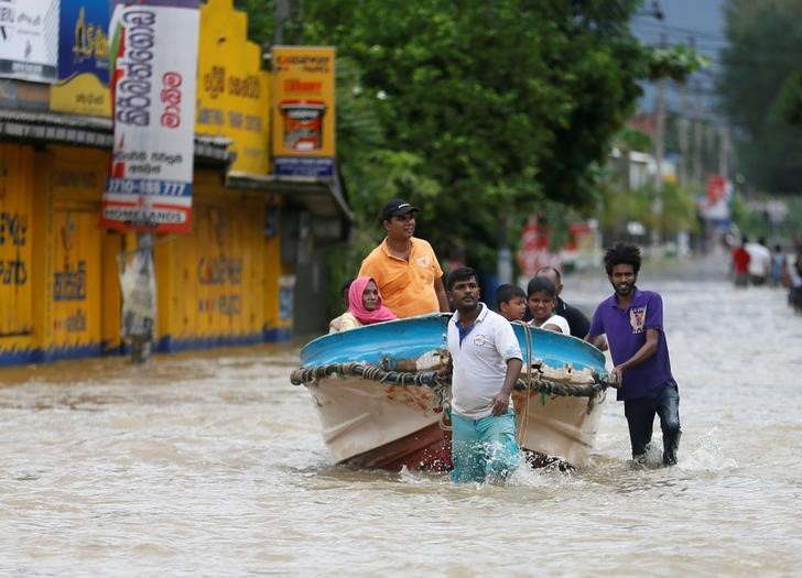Villagers pull a boat with people after rescuing them, on a flooded road in Biyagama, Sri Lanka May 17, 2016. REUTERS/Dinuka Liyanawatte