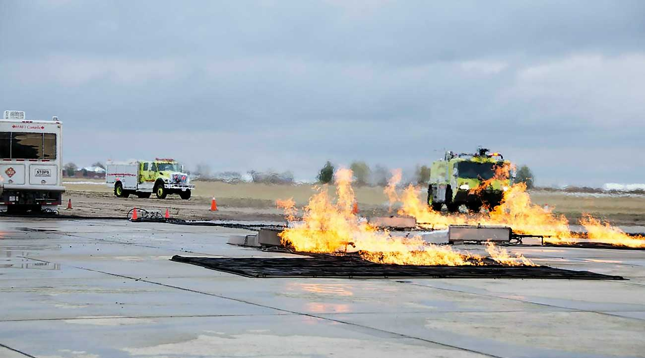 While using the Mobile Aircraft Fire Trainer (MAFT) to simulate a hard impact landing with breached fuel tanks, ARFF Trucks Red-6 and Red-8 moves into position to conduct firefighting operations.