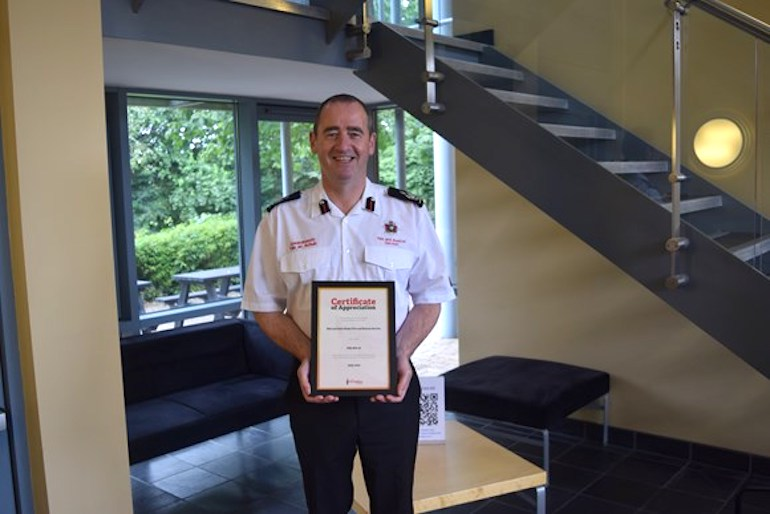 Deputy Chief Fire Officer Roger Thomas recieves the certifiacte of appreciation from the Fire Fighters Charity. (MWWFRS)